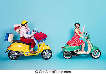 Full size profile photo of crazy shopaholic lady giving credit card assistant guy drive retro moped carry packs shopping abroad vintage clothes protective caps isolated blue color background