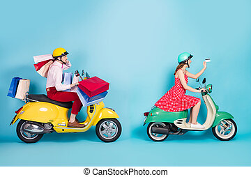 Full size profile photo of crazy shopaholic lady giving credit card exhausted guy drive retro moped carry packs shopping abroad vintage clothes protective caps isolated blue color background