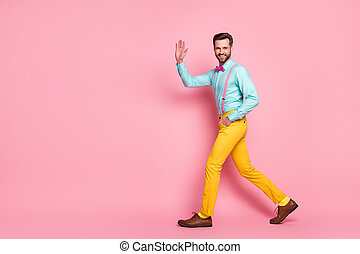 Full size profile photo of handsome guy trend stylish look walk red carpet celebrity waving hand wear shirt suspenders bow tie yellow pants footwear isolated pastel pink color background