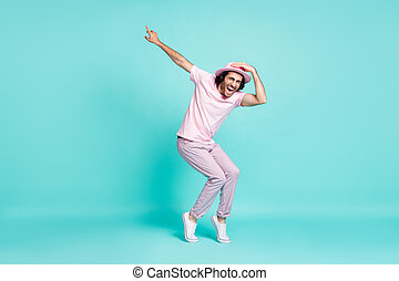 Full size profile photo of optimistic cool guy dancing wear spectacles pastel pink cap t-shirt pants sneakers isolated on teal background