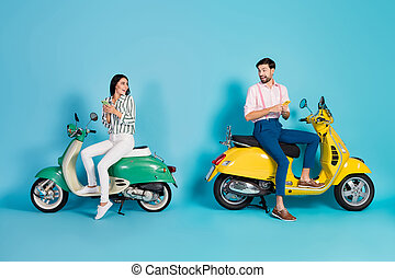 Full size profile side photo crazy surprised two people bikers driver sit yellow green motor bike use smartphone impressed gps map scream omg isolated blue color background