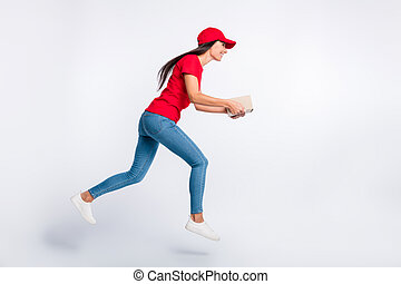 Full size profile side photo of young happy excited delivery girl running with parcel in hands isolated on grey color background