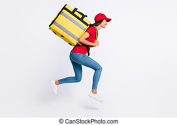Full size profile side photo of young happy smiling delivery girl with backpack running isolated on grey color background