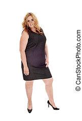 Full sized woman standing in black dress