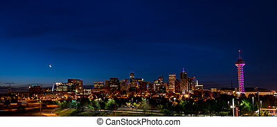 Full skyline of Denver Colorado at night with a moon