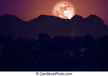 full strawberry moon on night red sky back over silhouette mountain