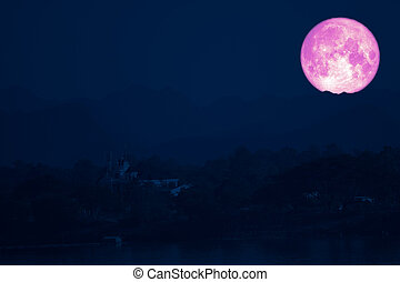 full strawberry moon on night sky back over silhouette mountain