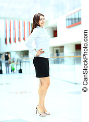 Fullbody business woman smiling in office