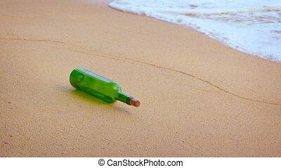 Green glass wine bottle rolls in the waves on a sandy beach...