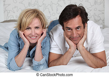 Fully dressed couple lying on a bed watching TV