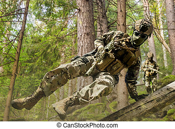 Fully equipped soldiers running and jumping in forest.