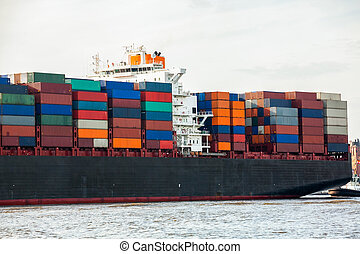 Fully laden container ship in port with its decks stacked with metal containers full of freight and cargo for international destinations