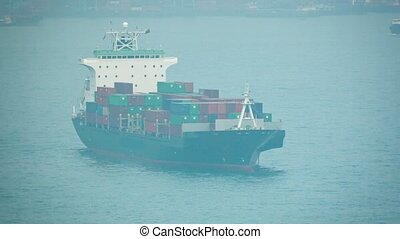Fully Loaded Container Ship Rides at Anchor in the Harbor