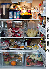 An open refrigerator door showing a full stocked fridge loaded up with food and fresh ingredients.