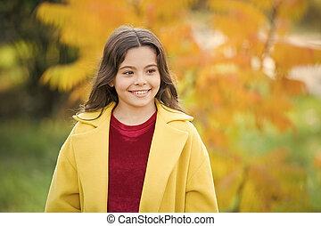 Fun activities for warm autumn days. Fall bucket list. Child cheerful on fall walk. Warm coat best choice for autumn. Autumn season concept. Kid girl wear coat for autumn weather nature background