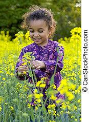 A beautiful mixed race girl looks having fun in a field full of yellow flowers