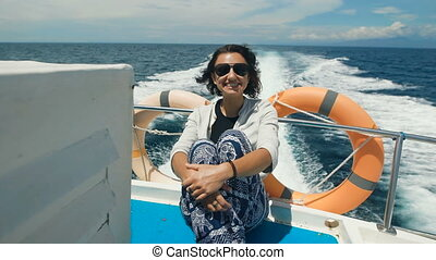 fun and tanned girl with black hair and glasses, blue pants and white blouse sitting on the yacht floor in the ocean