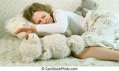 Fun awakening woman throwing a soft toy