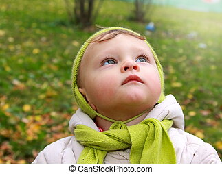 Fun baby looking up with serious thinking face outdoor. Closeup portrait on autumn background