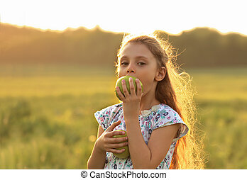 Fun beautiful kid girl with long hair joying and biting green apples on summer bright background. Closeup bright portrait