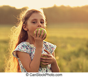 Fun beautiful kid girl with long hair joying and biting green apples on summer bright background. Closeup toned color portrait