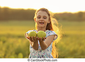 Fun beautiful kid girl with long hair joying and holding green apples on summer bright background. Closeup bright portrait