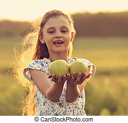 Fun beautiful kid girl with long hair joying and holding green apples on summer bright background. Closeup bright portrait. Toned