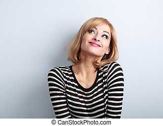 Fun beautiful thinking blond young woman in sweater looking up on blue background