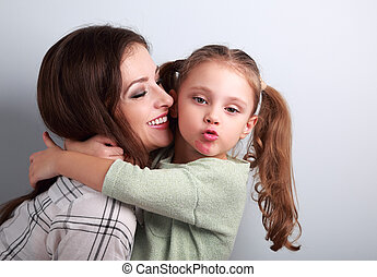 Fun bully kid girl showing kiss sign with mother lipstick kiss mark on chin and hugging her laughing mother