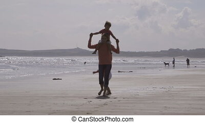 Fun by the sea - A happy young family of three walk along...