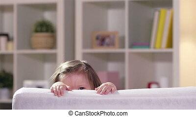 Fun - Charming child having fun hiding behind the sofa back