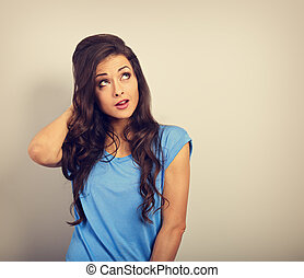 Fun confused grimacing casual woman looking up on blue empty copy space background with thinking look. Toned closeup portrait