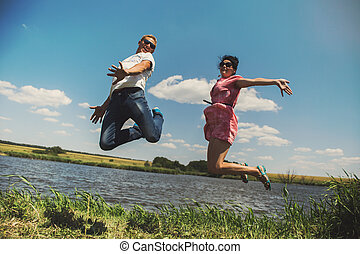 Fun couple in jump on the outdoor background