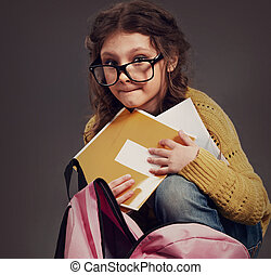 Fun cute pupil kid girl in eyeglasses hiding the exercies books with bad marks sitting near the backpack on grey background. Closeup