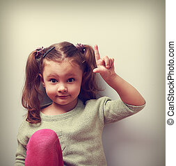 Fun emotion kid girl with good idea showing finger up on empty copy space. Closeup vintage color portrait