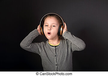 Fun emotional grimacing kid girl listening the music in...