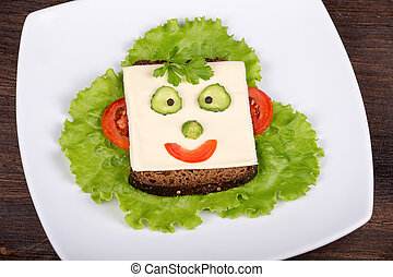 Fun food for kids - face on bread, made from cheese, lettuce...
