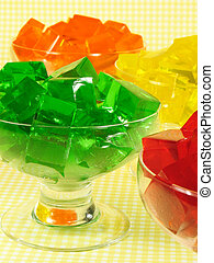Glasses of orange, green, red, and yellow cubed gelatin.
