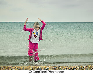 Fun girl throws up the cold sea water.