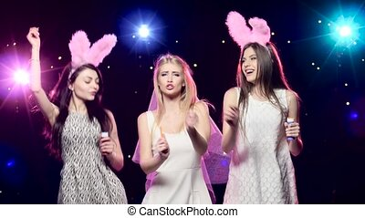 Fun girls at bachelorette party dancing and blowing soap bubbles
