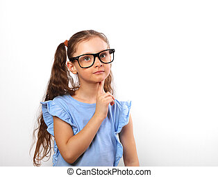 Fun grimacing happy girl in eye glasses thinking and looking up on background with empty copy spase.