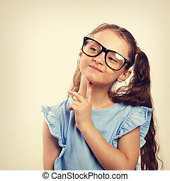 Fun grimacing happy girl in eye glasses thinking and looking up on background with empty copy spase. Toned vintage portrait