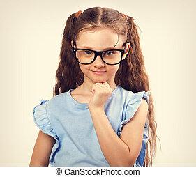 Fun grimacing happy girl in eyeglasses thinking and looking. Toned closeup vintage portrait
