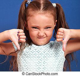 Fun grimacing kid girl showing thumb down on blue...