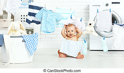 fun happy baby boy to wash clothes and laughs in laundry -...