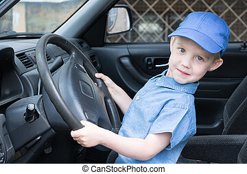 Fun, happy, boy is behind the wheel of the car and looking at us.