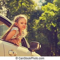 Fun happy enjoying traveling kid girl looking from the car window with open mouth on summer bright green nature background. Closeup portrait. Little driver. Kids safety.