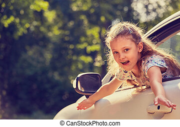 Fun happy enjoying traveling kid girl looking from the car window with open mouth on summer bright green nature background.