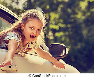 Fun happy enjoying traveling kid girl looking from the car window with open mouth on summer bright green nature background. Closeup