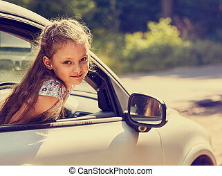 Fun happy enjoying traveling kid girl looking from the car window with open mouth on summer bright green nature background. Little driver. Kids safety